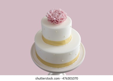 white wedding cake on pink background with pink rose and gold ribbons