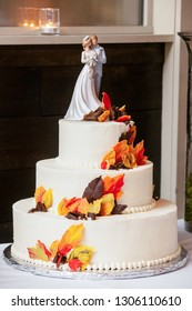 white wedding cake with orange and brown fondant icing fall colored leaves and a bride and groom on top