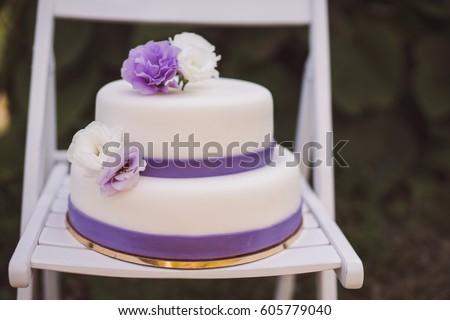 White wedding cake purple flowers decoration stock photo edit now white wedding cake with purple flowers decoration outdoors on wooden modern chair front view mightylinksfo