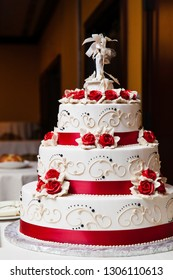 white wedding cake with red fondant icing flowers and red ribbons on each layer