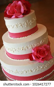 white wedding cake with red roses and pearls