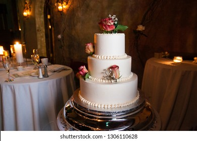 white wedding cake with red roses on a silver platter with a wedding table and candles in the background