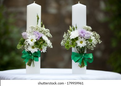 white wedding candles with bright beautiful flowers, isolated