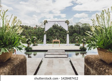 White Wedding ceremony arch in tropical jungle on edge of blue infinity swimming pool. Beautiful arch and decorations on the cliff.