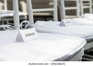 White wedding chairs with reserved signs closeup for ceremony with background of rows of many seats and nobody