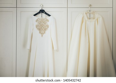 White wedding dress for bride hanging in the room