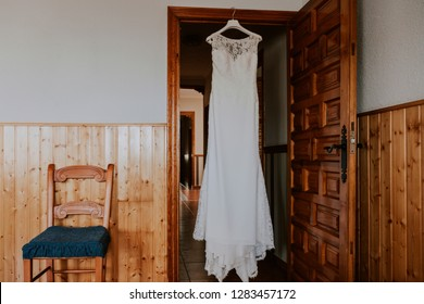 a white wedding dress hanging on a wooden door besides a chair in a rustic house