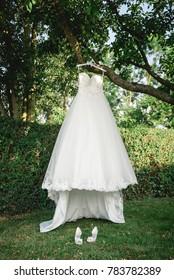 white wedding dress hanging on a tree