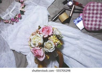 White wedding dress and pink wedding bouquet lying on the bed.