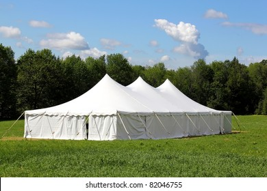 a white wedding or entertainment tent in a grass field on a sunny summer's day