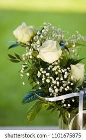 White wedding flowers, white rose, lily of the valley, ribbon outdoor, green background