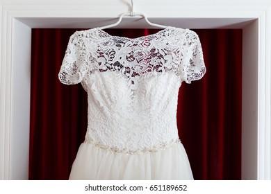 White wedding gown hanging at doorway.