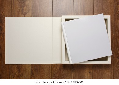 white wedding photo album on a wooden background with space for text. white family photobook in beige gift box with ribbon. family photoalbum in storage box with a beautiful  beige cover isolated
