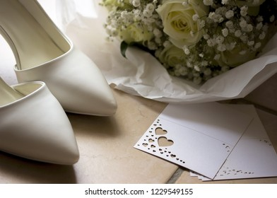 White wedding shoes with bouquet and card