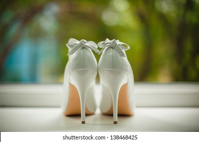 white wedding shoes with a bow on a heel on a green background