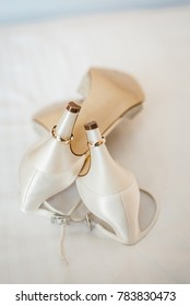 white wedding shoes with golden rings on it
