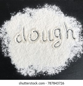 white wheat flour is scattered on a black surface, the inscription is a dough