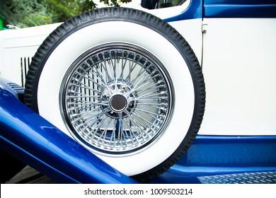 white wheel on a background of a radiator of a retro car. White hood retro car.