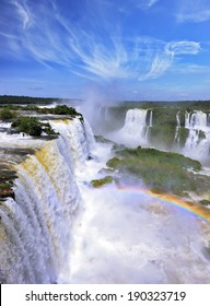 White whipped foam of water and a thin mist over the water.  Magnificent rainbow shines in the mist. The most high-water waterfall in the world - Iguazu. The picture is taken by lens Fisheye
