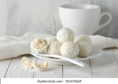 White whole and broken coconut candy balls in plate and cup on rustic wooden background. White food styling.