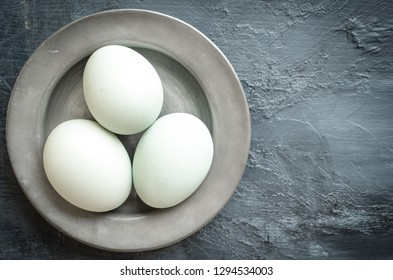 White whole eggs on pewter dish and grey background