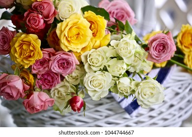 A white wicker basket overflowing with petit roses in assorted colors