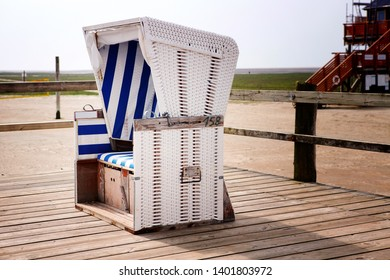 white wicker beach chair on wooden deck by the beach