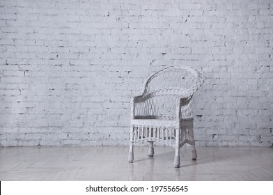 White wicker chair standing in an empty room in front of a brick wall on light parquet floor. Natural light from the window, reflection on the floor. Copy space