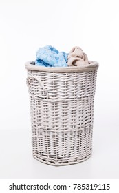 White wicker laundry basket full with dirty towels
