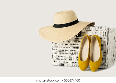 White wicker suitcase,  female hat and yelow shoes.