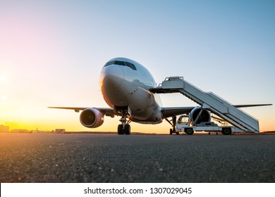White wide body passenger aircraft with a boarding steps at the airport apron in the evening sun