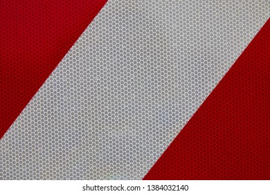 white wide diagonal line on a bright red background, honeycomb texture with light reflectors inside