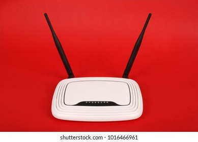 White WI-FI router with two antennas isolated on red background