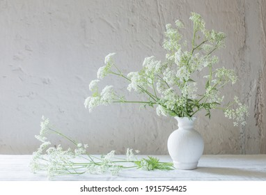 white wild flowers in vase on white background