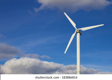 White wind turbine standing in front of a bright summer sky
