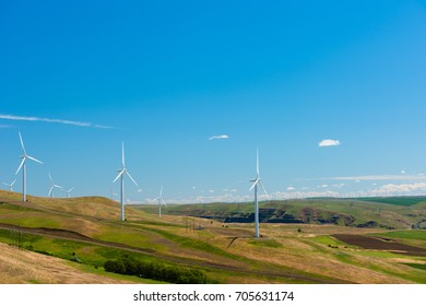 white windmills producing clean energy during a bright summer day helping fight against global warming
