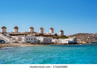 White windmills with a thatched roof on the island of Mykonos at morning light near the sea. Greece.