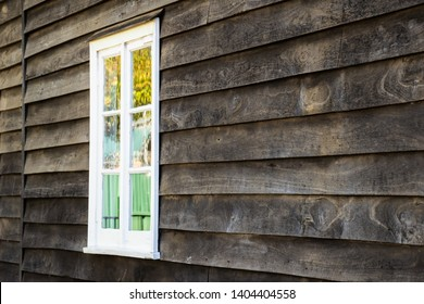 White window frame with colourful curtain in greying raw wooden weatherboard wall