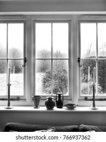 white window frame, with window sill with 2 candles and glass ornaments on white window sill, view through window is garden shrubs