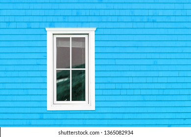 White window on blue shingled wall. Typical colourful architecture of Iles de la Madeleine in Canada. Space for your text.