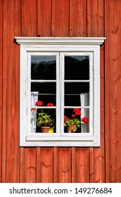 White window with red flowers on an old tree house facade