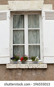 White window with shutters and flower pot