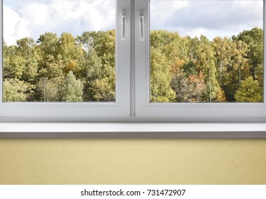 White window with sill and autumn landscape, interior with window in autumn day