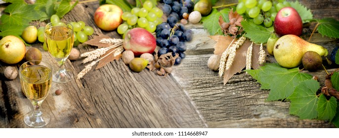 White wine and autumnal fruit- harvest on rustic wooden table