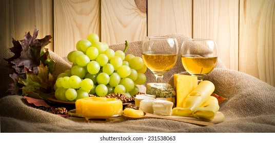 White wine with blue, camembert and swiss cheese, walnuts, honey and grapes on sackcloth on a background of a wooden wall and autumn leaves