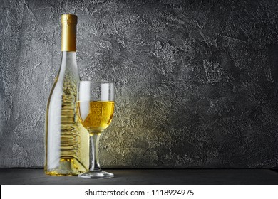 White wine bottle and glass for tasting in dark cellar on gray concrete background