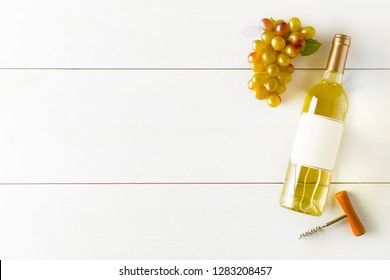 White wine bottle with grapes and corkscrew on white wooden table flat lay from above with copy space