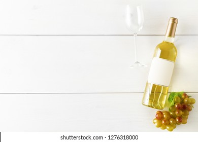 White wine bottle with grapes and wine glass on white wooden table flat lay from above with copy space