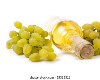 White wine in bottle and grapes isolated on white background