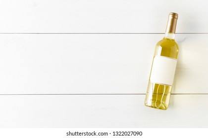 White wine bottle on white wooden table flat lay from above with copy space